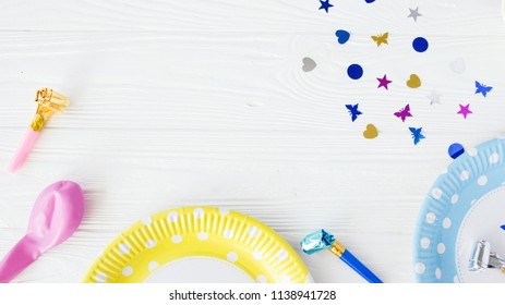 Children birthday flat lay with yellow and blue paper plates,confetti,balloon.Celebration flat lay with design space.Holiday themed top view with place for text.Children birthay background.