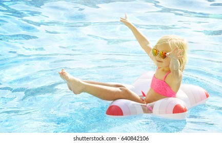 Children blond girl enjoying summer vacations at the swimming pool