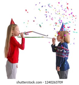 Children blowing party trumpets with confetti celebrating new year