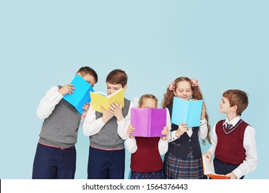 Children with books in the studio on a blue background. Education concept. Back to school.