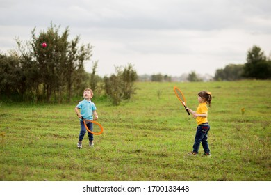 children - a boy in a blue T-shirt and a girl in yellow play tennis with rackets and a ball on nature