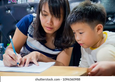 children boy doing homework with mother, kid write paper, education concept