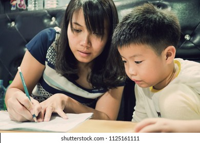children boy doing homework with mother, kid write paper, family concept, learning time, student