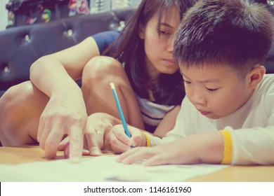 children boy doing homework with mother, kid write paper, family concept, learning time, student, back to school