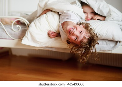 Children, boy and girl indulge on the bed in the bedroom. They slip out of bed, pulling the bedclothes. Children are very fun.