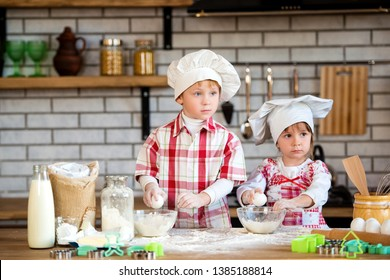 Children a boy and a girl prepare delicious gingerbread and cookies in the kitchen from flour and eggs