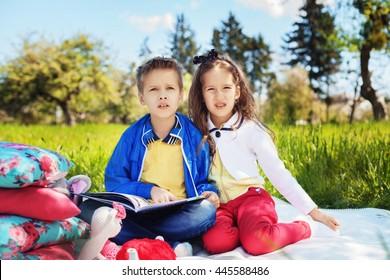 children, a boy and a girl reading a book in the garden