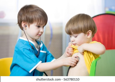 Children boy playing doctor in playroom or kindergarten