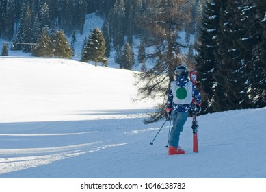 children, boy who has skied on slopes, after ski lesson with instructor who teaches him, sunny day, evening, sunset, shadow, winter, Alps, Madonna di Campiglio, South Tyrol, Italy
