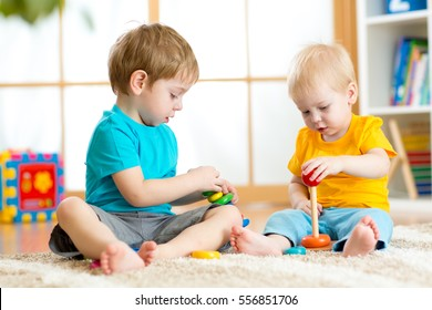 Children boys play with educational toys in preschool or kindergarten. Toddler kid and baby build pyramid toys at home or daycare.
