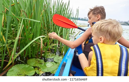 Children boys swim on a plastic kayak boat on the lake with water lilies.