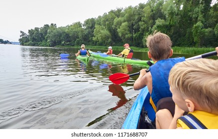 Children boys travel with their parents dad and mom on plastic kayaks along the river