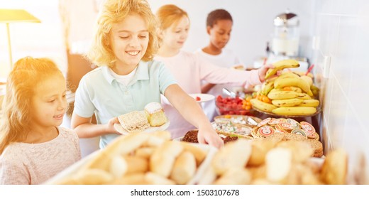 Children bring food at the buffet of a canteen