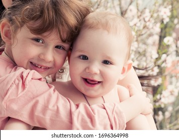 Children brother sister infant together happy nature blossom flowers