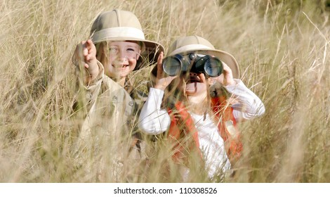 Children brother and sister playing outdoors pretending to be on safari and having fun together with binoculars and hats