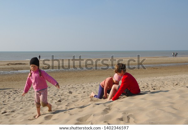 Children, brother and two sisters and puppy cavalier king charles spaniel playing in the dunes in holland