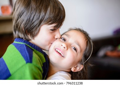 children brothers kiss on the cheek laughing and playing at home