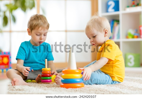 children brothers playing together in nursery at home