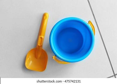 Children bucket and shovel on tile floor