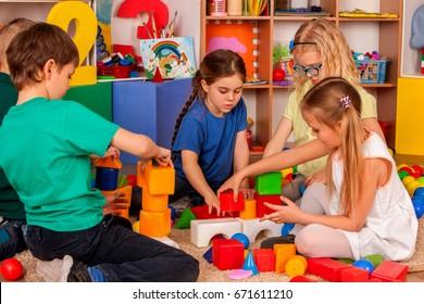 Children building blocks in kindergarten. Group kids playing toy on floor in interior preschool. Building tower of cubes. Independent children's creativity