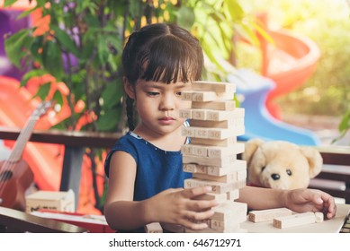 Children building wood blocks at playground. Girl kid playing stacking wood blocks (Jenga games) for meditation practice.Hand movement control Building Computational Skills Children's play concept.