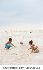 Children burying father in sand