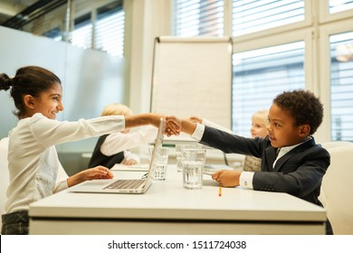 Children as businessmen greet each other with a handshake before the negotiations