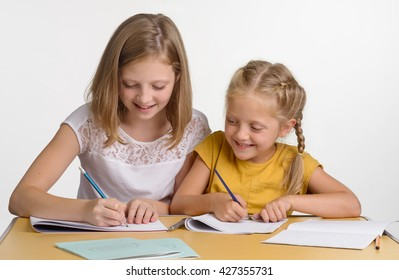 Children are busy with drawing pictures in their albums with pencil and brush. Young child looks on sister's work. Lovely young ladies smile.