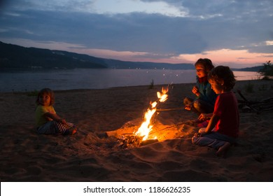 children camping on beach and sitting by the fire  on a summer evening