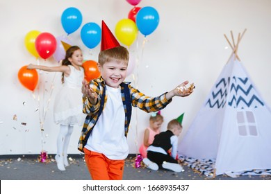 Children in caps and elegant clothes have fun and enjoy their birthday with balloons.