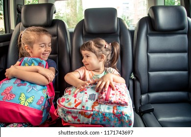 Children in the car go to school, happy, sweet faces of sisters, pupils of a kindergarten with school backpacks, sitting in the parental car