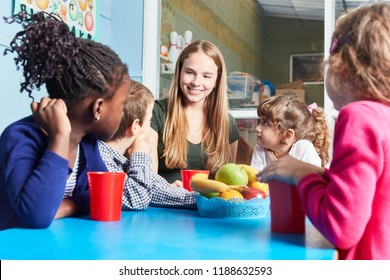 Children and carer together eat fruit as a snack in the kindergarten or daycare