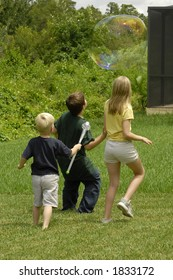 Children chasing a large soap bubble in the back yard.