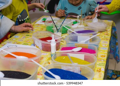 Children cheerfully spend time with color sand