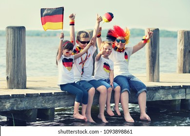 Children cheering and supporting German national football team. Kids fans and supporters of Germany during soccer championship