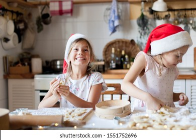 Children chefs are cooking Christmas cookies in cozy home kitchen. Happy kids in santa hats are enjoying preparation holiday meal. Girls are baking Xmas biscuits together. Lifestyle moments.