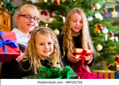 Children with Christmas gift on Christmas day in family home under tree
