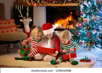 Children at Christmas tree and fireplace on Xmas eve. Family with kids celebrating Christmas at home. Boy and girl in matching pajamas decorating xmas tree and opening presents. Holiday gifts for kid.