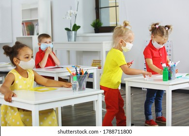children in the classroom in medical masks for respiratory protection, mixed race