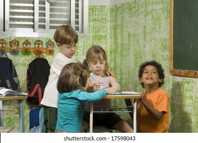 Children in a classroom.  They are working together.  Horizontally framed shot.