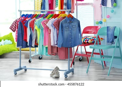 Children clothes hanging on hangers in the shop