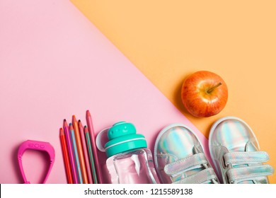 Children clothes and study stuff: sneackers, pencils, bottle of water and electron gps watches on pink background. Flat lay, top view. Copyspace for text.