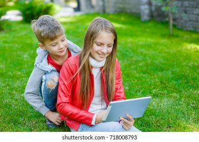 children communicate using a tablet computer on green grass