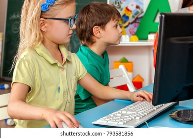 Children computer class for education and video game. Girl won boy in logical computer game sitting near monitor. Kids play on computer. Simulator for training keyboard.