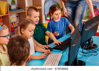 Children computer class us for education and video game. Kids boy and girl play and learn on computer. Simulator for training keyboard.