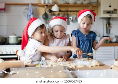 Children are cooking Christmas cookies in cozy home kitchen. Cute kids in santa hats preparation holiday dinner for family. Three sisters bake Xmas biscuits. Lifestyle moments. Children chef concept.