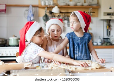 Children are cooking Christmas cookies in cozy home kitchen. Cute kids in santa hats preparation holiday dinner for family. Three sisters bake Xmas biscuits. Lifestyle moment. Children chef concept.