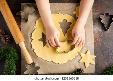 Children is cooking Christmas cookies, cut the dough with cookie cutter, family traditions, delicious sweet holiday food