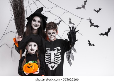 Children in costumes celebrating Halloween, against the background of bats and cobwebs