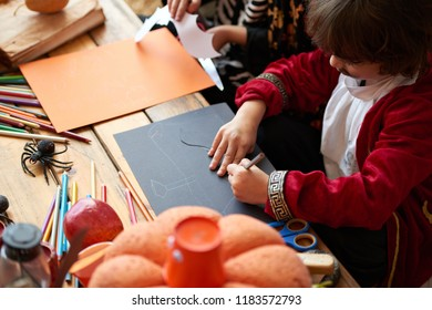 Children in costumes making Halloween decorations out of colored paper in kindergarden